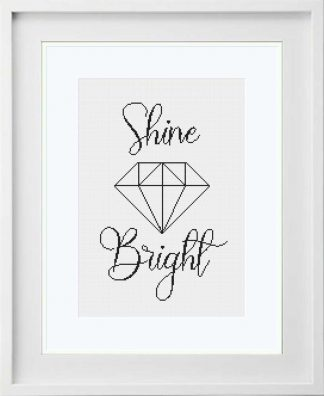 SHINE BRIGHT cross stitch pattern mounted in a white frame